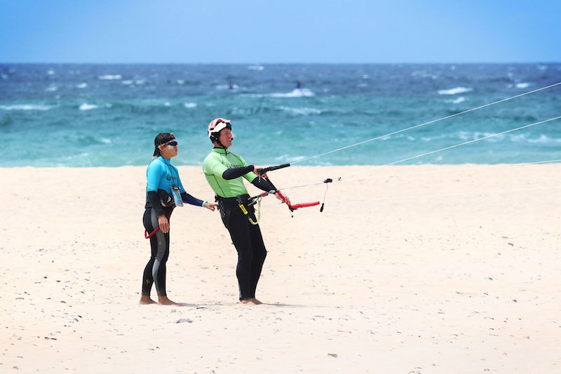 Man learning to fly a kitesurfing kite on the beach in Tarifa while his instructor holds his harness.