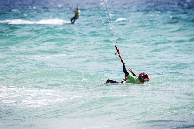 Man leaning back in the water learning to kitesurf in Tarifa, Spain.