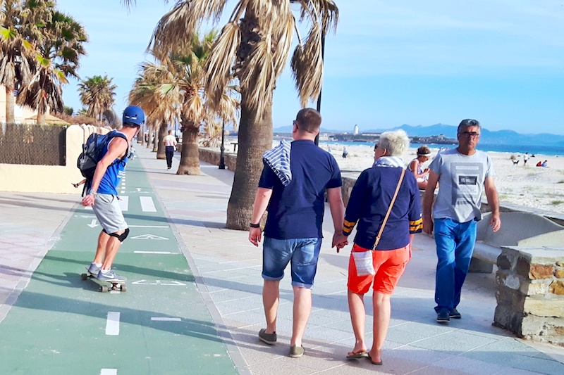 Man long boarding with helmet on and other people walking along the boardwalk in Tarifa, Spain.