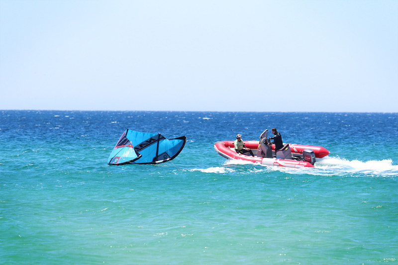 Blue kite in the water and a red rescue dinghy in the blue waters in Tarifa, Spain.