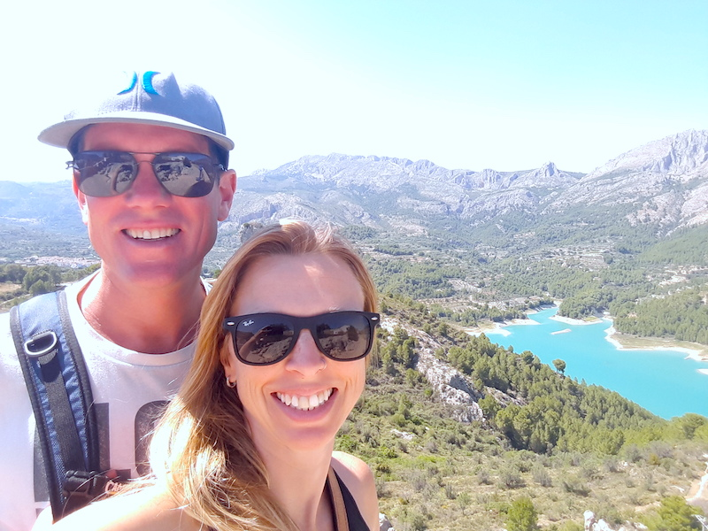 Couple smiling with bright blue reservoir behind surrounded by mountains in Castell de Guadalest, Spain.