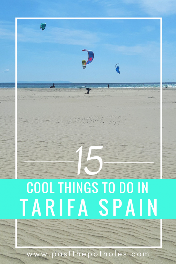Endless stretch of sand with many people kiteboarding and text: 15 cool things to do in Tarifa Spain.