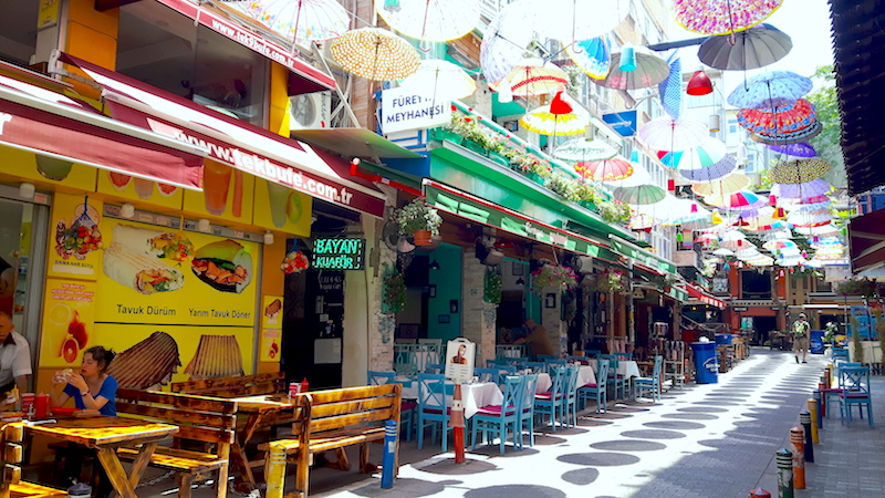 Colourful street filled with outside restaurant tables and covered with a grid of umbrellas in the Asian side of Istanbul, Turkey.