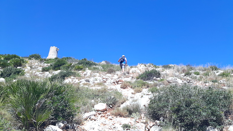 Man hiking up a steep, rocky hillside to an old watchtower at the summit in Denia, Spain.