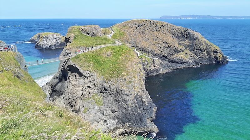 A rope bridge connecting a small rock island from mainland Northern Ireland across bright turquoise water.