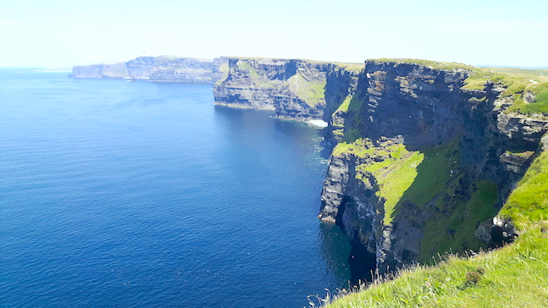 View across the rugged Cliffs of Moher and the blue Atlantic Ocean in Ireland.