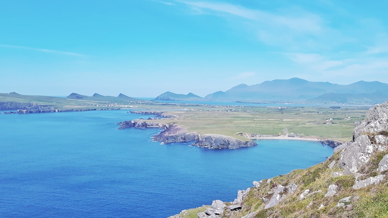 View across the Dingle Peninsula from Clogher Head of rugged green hills and bright blue water on the Dingle Peninsula, Ireland.