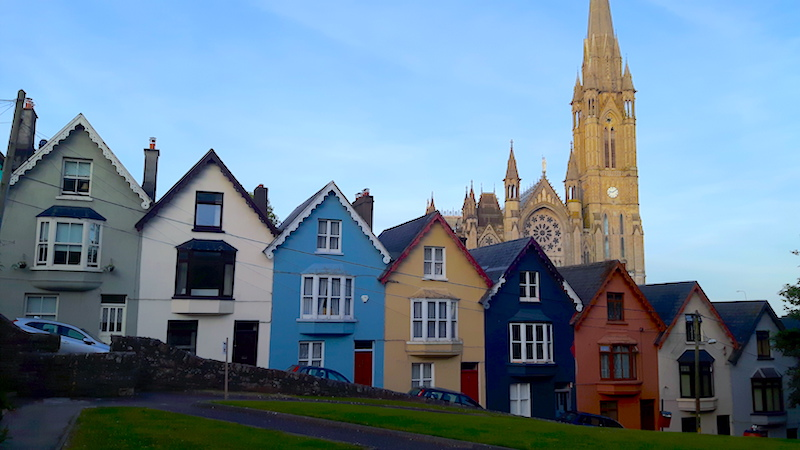 Colourful row of houses in front of a tall church lit by the setting sun in Cobh, Ireland.