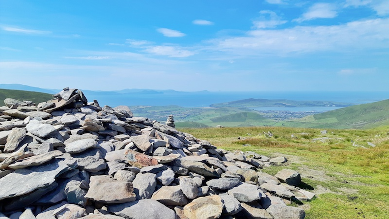 Large stack of rocks on top of Conor Pas with a stunning view across Irish landscape.
