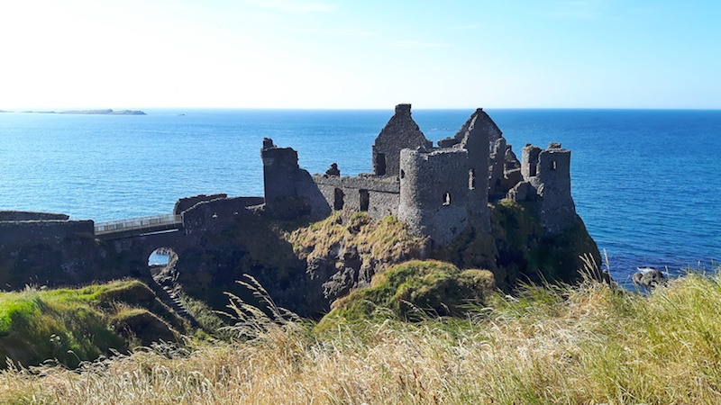 Ruins of Dunluce Castle perched on the cliff edge overlooking the sea Northern Ireland.