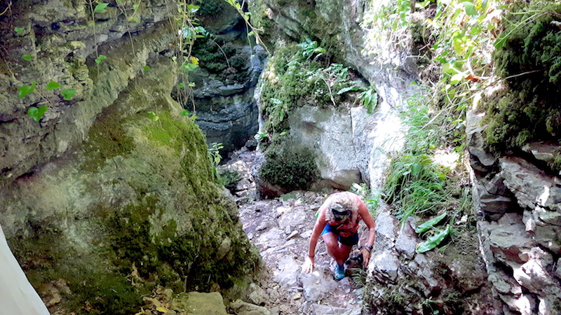 Woman climbing through a narrow gorge called Ebbor Gorge, Wookey Hole UK