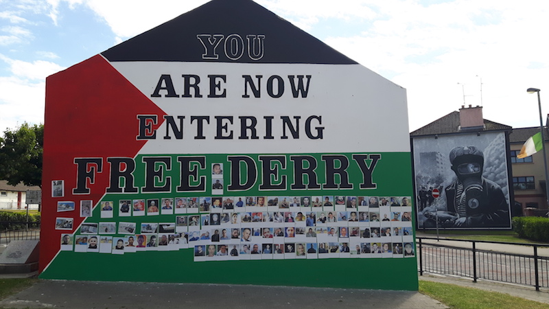 Wall painted with text: You are now entering Free Derry and a mural on a building behind from the 'troubles' in Northern Ireland.
