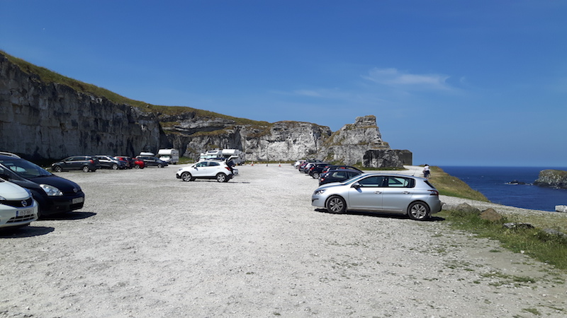 Cars parked in an old quarry along the north coast of Northern Ireland at Carrick-a-Rede rope bridge.