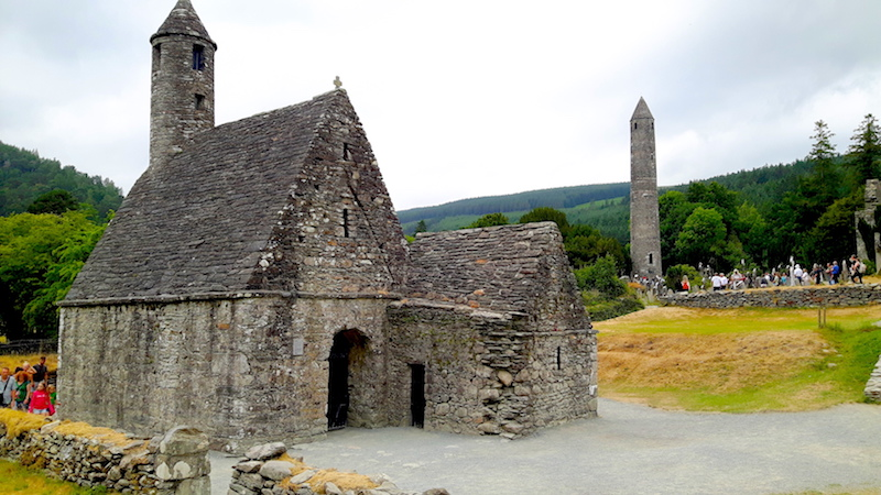Ancient chapel and tower surrounded by nature in Glendalough Monastic Site, Ireland