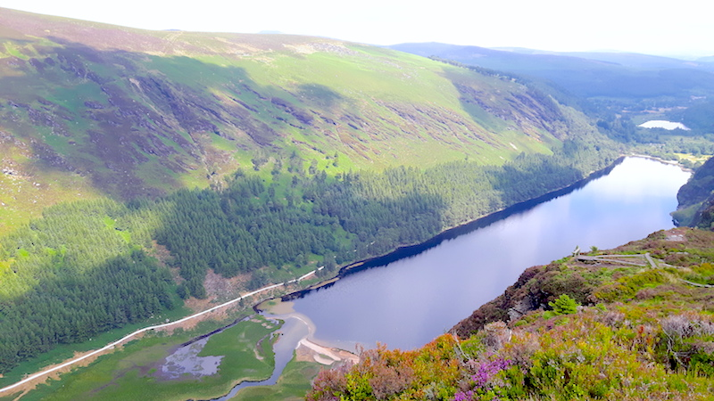 View of long, thin lake surrounded by lush green hills in Glendalough, Ireland.