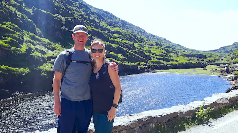 Man and woman in front of a picturesque lake with rock covered hill in Gap of Dunloe, Ireland.