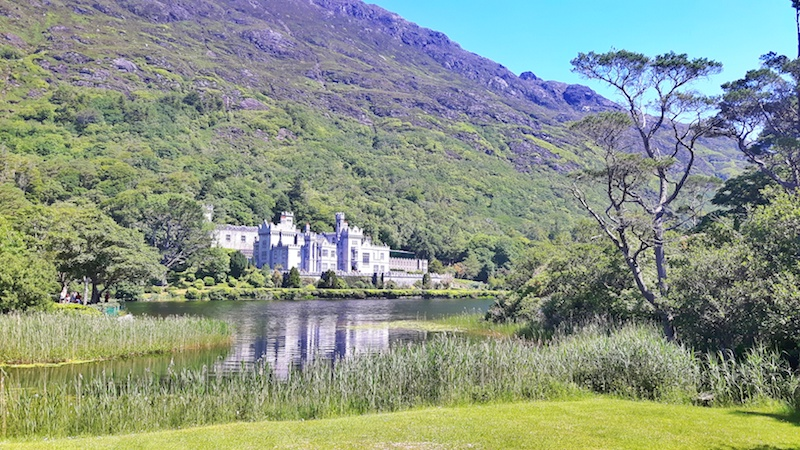 Huge, ornate building of Kylemore Abbey on the edge of a lake in Connemara National Park, Ireland.