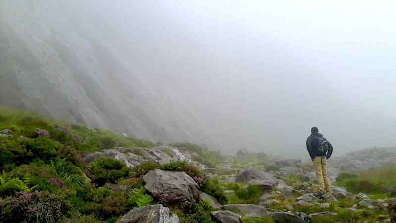 Sheer cliff face with a rocky landscape shrouded in clouds at Llyn Ogwen, Wales.