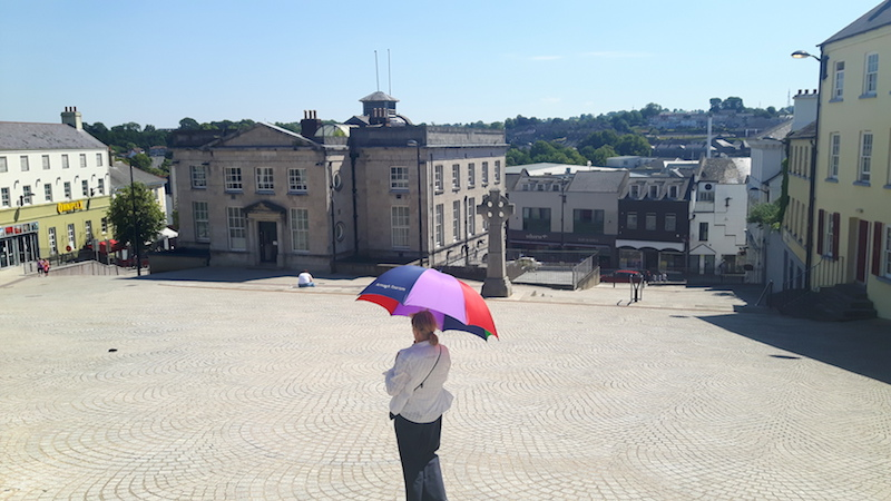 Walking tour guide holding an umbrella in the large open market square of Armagh, Northern Ireland.