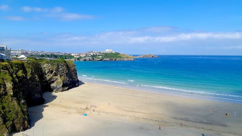 Picture perfect beach surrounded by cliffs and turquoise water in Newquay, Cornwall UK