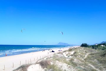 Long sandy beach with mountain in the distance and kites in the sky at Oliva, Spain.
