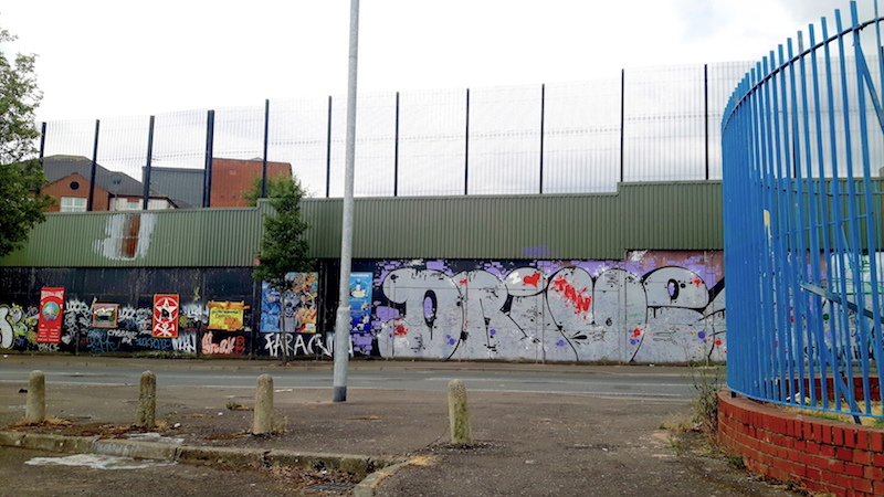 Graffiti covered concrete wall with tall wire fence above. The peace wall in Belfast, Northern Ireland.