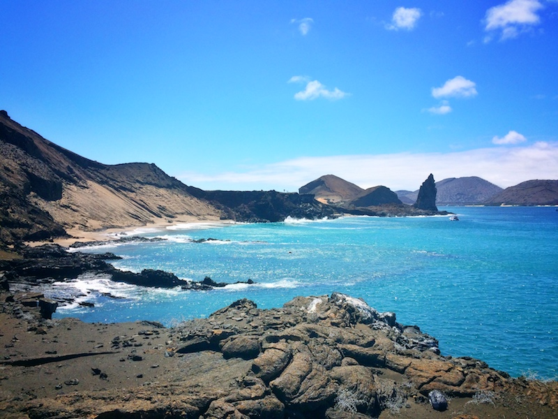 Bright blue waters against dark volcanic rock of Bartolome Island in Galapagos.