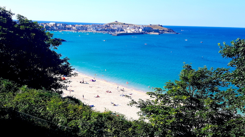 Busy white sand beach with turquoise water between the trees in St. Ives, Cornwall, England.