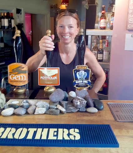Woman pulling a pint of Potholer beer in Wookey Hole pub, UK.