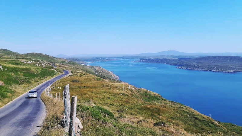 An oncoming car along the narrow winding road running on the edge of a hill down to the bright blue water in Ireland.