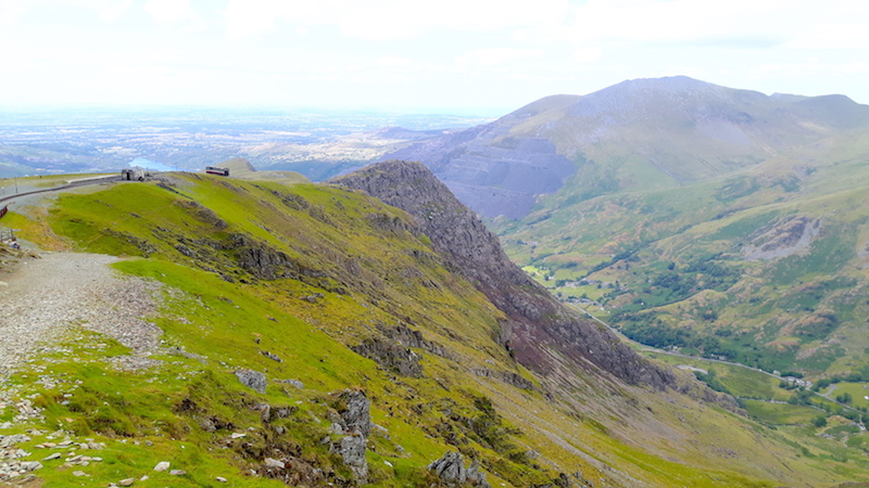 Steam train climbing Mount Snowdon with view across valley, Wales.