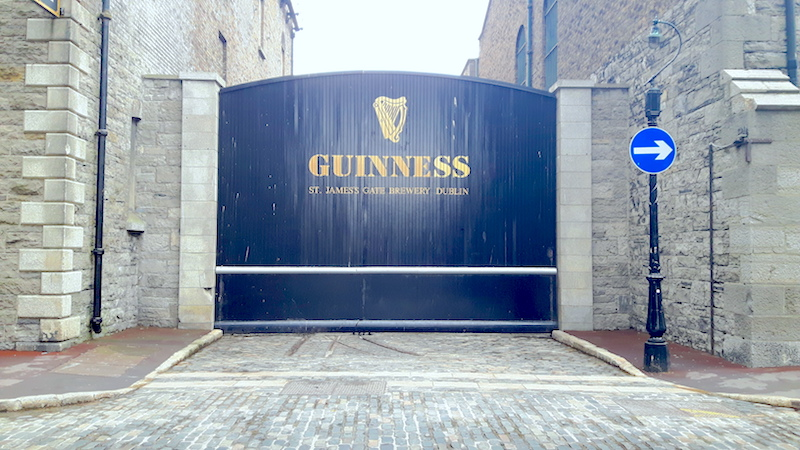 Black gate with gold lettering at St James's Gate Guinness Brewery in Dublin, Ireland.