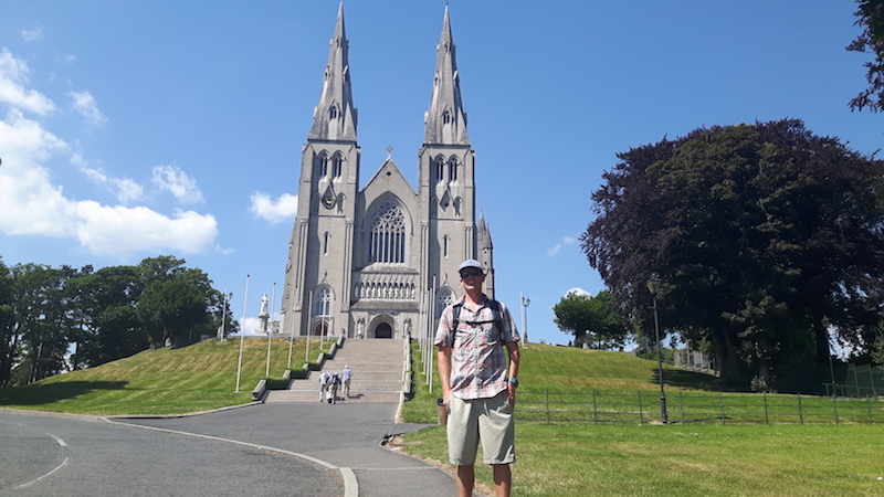 Man standing in front of the grand facade of St Patrick's Catholic Cathedral in Armagh, Northern Ireland.