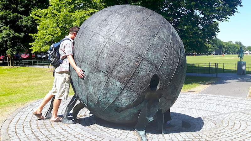 Man looking into a giant metal globe in a park in Armagh, Northern Ireland.