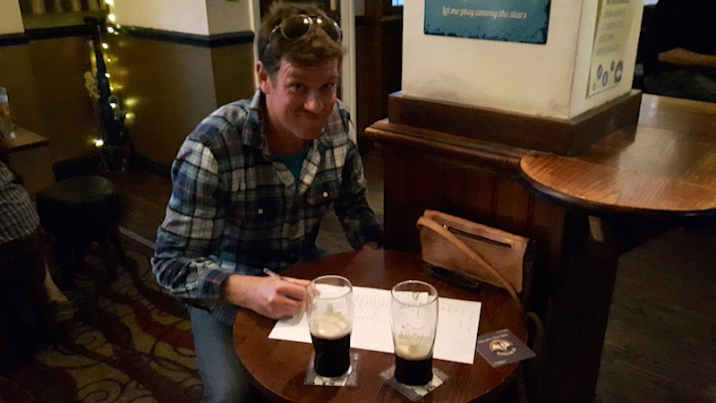 Man taking a pub quiz with Guinness on the table in Conwy, Wales.