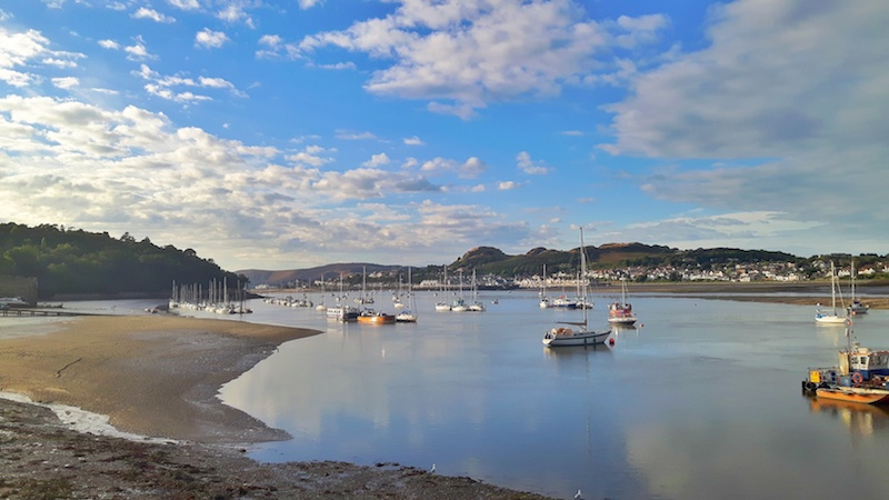 Boats at low tide in the river in Conwy, Wales.