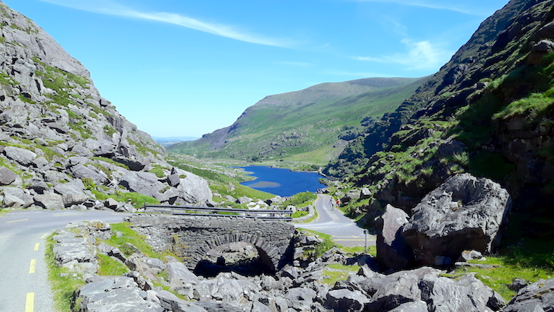 Winding road over a stone bridge with a blue lake in the middle of green hills in Gap of Dunloe, Ireland.