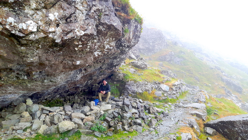 Man taking shelter under a huge boulder on a wet, cloudy hiking trail in Llyn Ogwen, Wales.