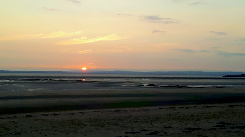 Sunset across a wide bay in Kewstoke, Somerset, UK.