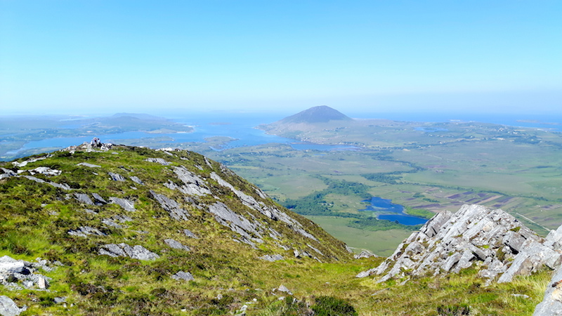 View of green hills and blue Atlantic Ocean from the top of Diamond Hill in Connemara National Park, Ireland.