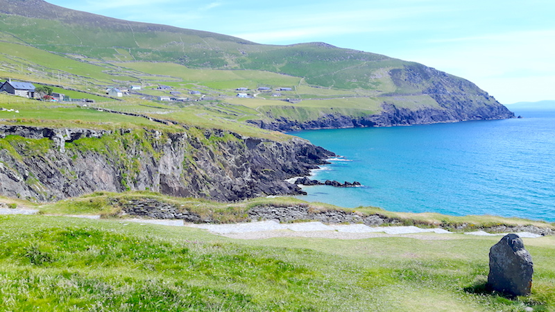 Jagged black cliffs and bright green hills and blue ocean on Slea Head Drive in Dingle, Ireland.