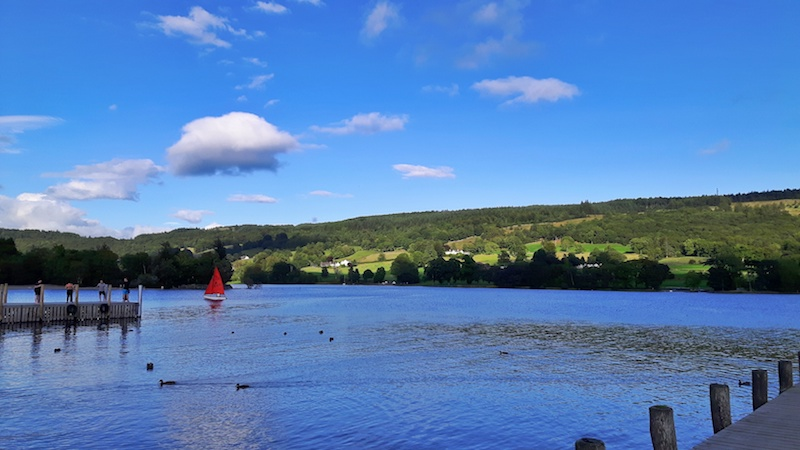 Red sailboat on a blue lake surrounded by green hills in Coniston Waters, Lake District, England.