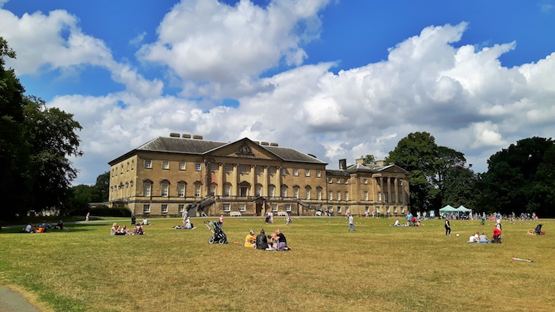 Large stone mansion called Nostell Priory with people relaxing on the grass in front in Yorkshire, UK.