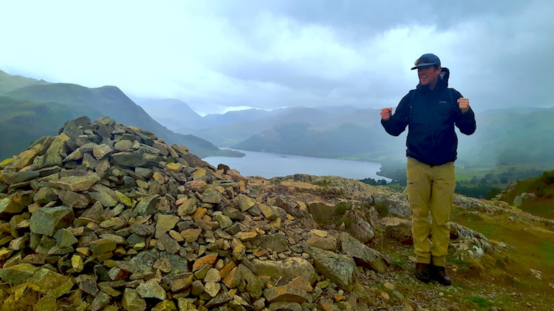 Man celebrating reaching Yew Crag summit in Ullswater, Lake District with view to the lake on a stormy day in England.