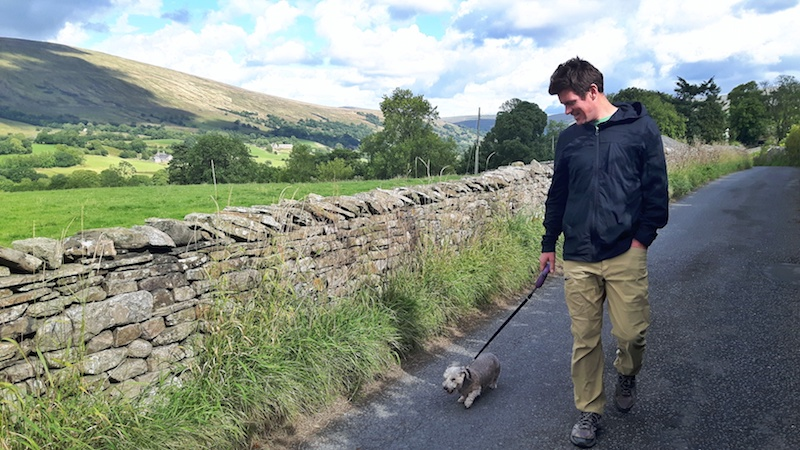 Man walking a small dog down a country lane in the Yorkshire Dales, England.