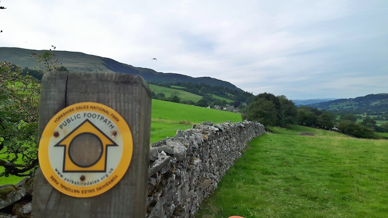 Yellow sign to mark a hiking trail across the Yorkshire Dales attached to a dry stone wall. England.