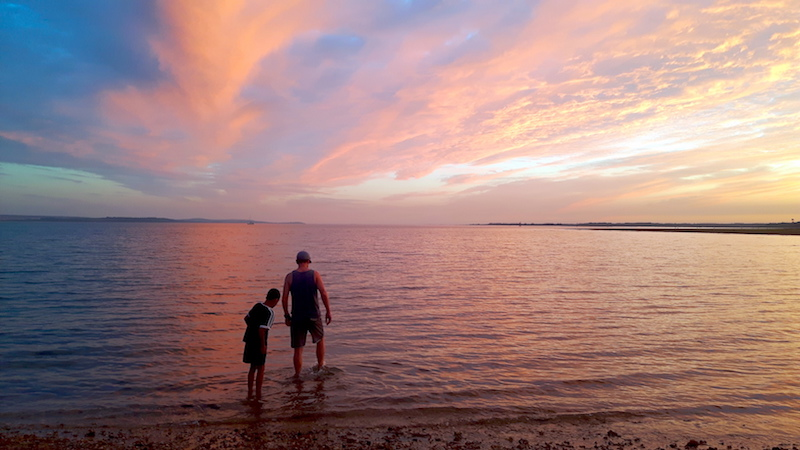 Man and boy paddling in Lepe Beach at sunset, England.