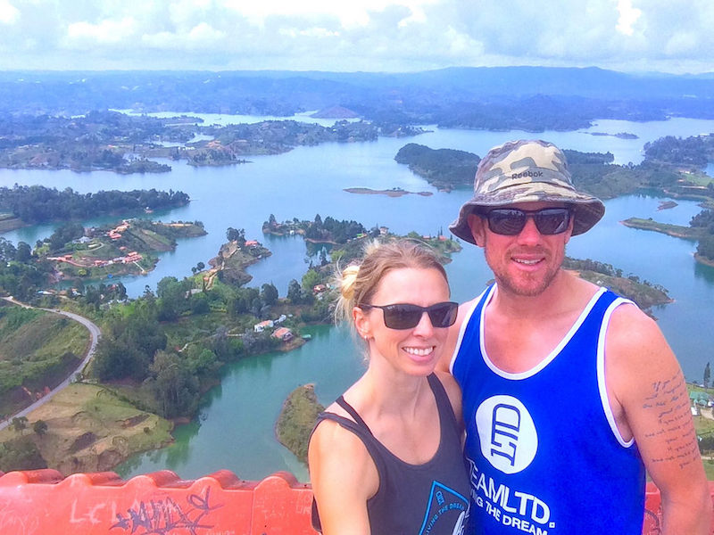 Couple smiling with a view of blue lakes and green islands of Guatape, Colombia.
