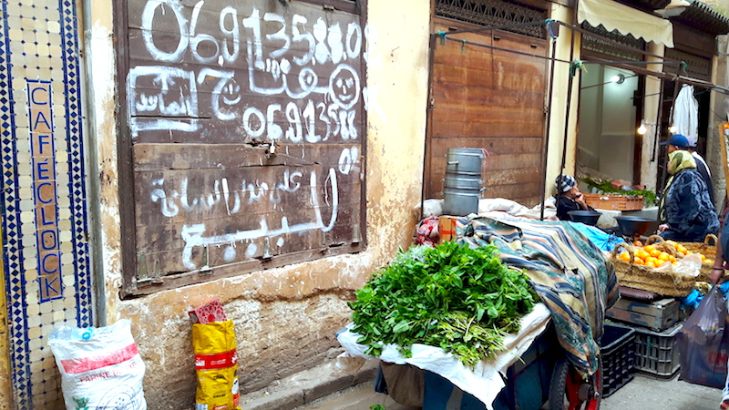 Arabic signs, fresh herbs for sale on a cart in an alleyway in Fes Medina, Morocco.