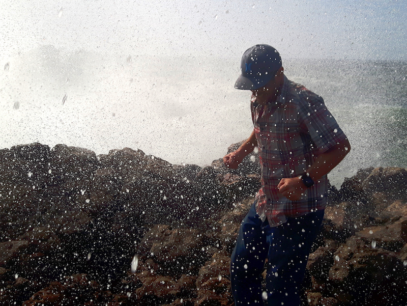 Man getting soaked from a surprise wave crashing over sharp rocks in Bordeira, Alentejo region, Portugal.